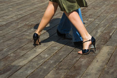 Street Tango Legs. Female and male legs dancing tango on a wooden deck of a public dancing floor Stock Photo