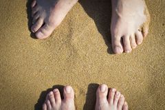 Female and male legs on sand, top view stock images