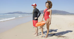Female and male lifeguards posing on beach Stock Photos