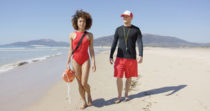 Female and male lifeguards walking along beach Royalty Free Stock Photography
