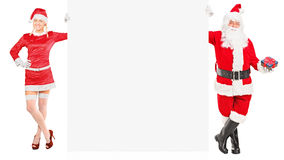 Female and male like Santa Claus holding a panel. Full length portrait of a female and male Santa Clauses holding a white panel on white background Royalty Free Stock Photos