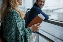 Glad man and woman going on a plane. Female and male people preparing for the flight. Focus on women holding wallet and tickets Stock Photos