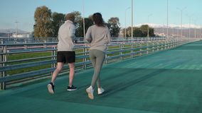 Female and male runners are training on open stadium, back view stock video