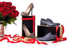 Female and male shoes on boxes and bunch of roses. Female and male shoes on gift boxes and bunch of roses over white background Stock Photos
