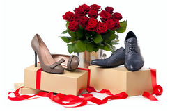 Female and male shoes and bunch of roses. Female and male shoes on gift boxes and bunch of roses over white background Stock Image