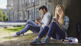 Female, male strangers sitting under tree, using cellphone, girl looking worried. Stock footage Royalty Free Stock Images