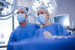 Female and male surgeon wearing surgical mask in operation theater. At hospital Stock Images
