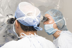 Female and Male Surgeons Using Operating stock images