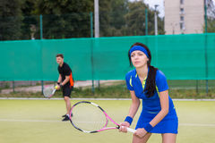 Female and male tennis players playing doubles outdoors Royalty Free Stock Image