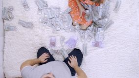 Female and male throw at each other a lot of banknotes of dollars on the bed, slow motion, top view.  stock video