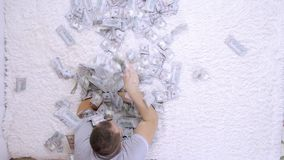 Female and male throw at each other a lot of banknotes of dollars on the bed, slow motion, top view.  stock video footage