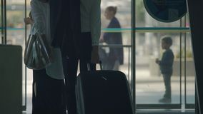 Female and male travelers walking out through airport automatic opening doors. Stock footage stock footage