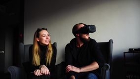 Female and male two friends spend leisure time together with gadgets and guy in VR glasses, sitting in armchairs in stock video footage