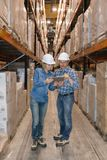 Female and male worker looking up in warehouse. Female Stock Images