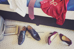 Female and man footwear and clothing in a hotel room. Female and man footwear and clothing in a hotel room, vintage toned conceptual picture Stock Images