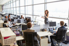 Female manager addressing workers in open plan office Royalty Free Stock Photography