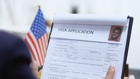 Female manager checking USA visa application, marking denied, travel forbidden. Stock footage stock footage