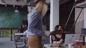 Female manager comes to business team. Mixed race group of people meeting in office. Camera moves up from legs. slow mo. Female blonde manager comes to creative stock footage