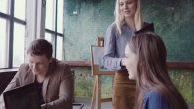 Female manager comes to business team. Mixed race group of people meeting in office. slow mo. Female blonde manager comes to creative business team. Mixed race stock video footage