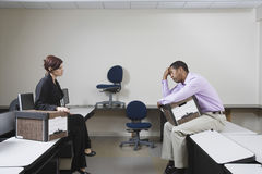Female Manager And Depressed Man Sitting On Desk Royalty Free Stock Photo