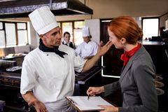 Female manager and male chef interacting with each other in kitchen royalty free stock image