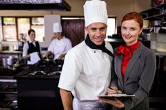 Female manager and male chef writing on clipboard in kitchen stock photos