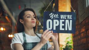 Female manager opening coffee shop in morning hanging open doorplate smiling