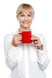 Female manager posing with coffee mug in hand Royalty Free Stock Image