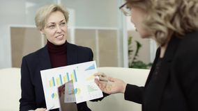 A female manager presents new project plan to colleagues at meeting, explaining ideas on flipchart to coworkers in. Office, businesswoman gives presentation stock video footage