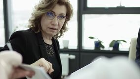 A female manager presents new project plan to colleagues at meeting in office, businesswoman gives presentation stock video