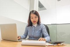 Female manager reading financial report and working on laptop stock photo