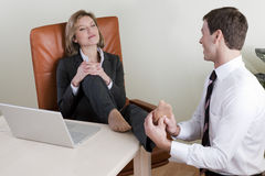 Female manager receiving feet massage. From  male colleague Royalty Free Stock Photos