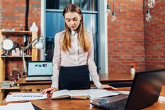 Female manager standing at her workplace planning her working day reading notes made in notebook Royalty Free Stock Image
