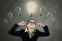 Female manager thinking idea under lightbulbs. Attractive young businesswoman concentrate to find idea under light bulbs Royalty Free Stock Photography