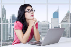 Female manager thinking idea in workplace. Beautiful businesswoman sitting in the office with laptop computer on the table and looks thinking something Stock Photos