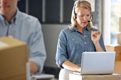 Female Manager Using Headset In Distribution Warehouse. On Laptop Royalty Free Stock Image