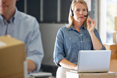 Female Manager Using Headset In Distribution Warehouse. On Laptop Stock Photos
