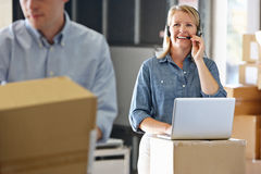 Female Manager Using Headset In Distribution Warehouse. Smiling Stock Image