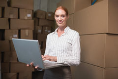 Female manager using laptop in warehouse Stock Photo