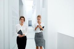 Female managing director with touch pad walking down company hallway while her secretary checks working schedule on two mobile pho. Businesswoman using cell Royalty Free Stock Image
