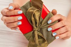 Female manicured hands holding gift box. Woman hands with winter nails design holding Christmas gift box. Holidays and celebrations concept Royalty Free Stock Photo
