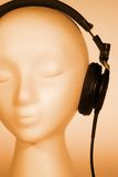 Female Mannequin listening to Music. Female mannequin head listening to music with orange overlay royalty free stock image