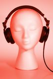 Female Mannequin listening to Music. Female mannequin head listening to music with red overlay Royalty Free Stock Image