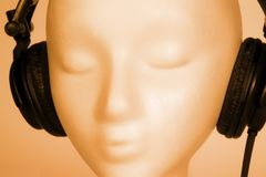 Female Mannequin listening to Music. Female mannequin head listening to music with red overlay stock photography