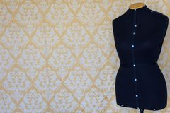 Female mannequin for tailoring. Wallpaper with pattern in the background royalty free stock image
