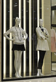 2 Female mannequins wear Autumn winter dress in a fashion clothing shop window Royalty Free Stock Photo