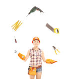 Female manual worker juggling with tools Stock Image