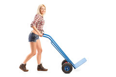 Female manual worker pushing an empty handtruck Royalty Free Stock Images