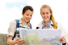 Female map hike. Two cheerful women hiking outdoors and consulting their map for the direction in which to travel stock images