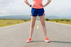 Female marathon runner standing on country road Royalty Free Stock Photos